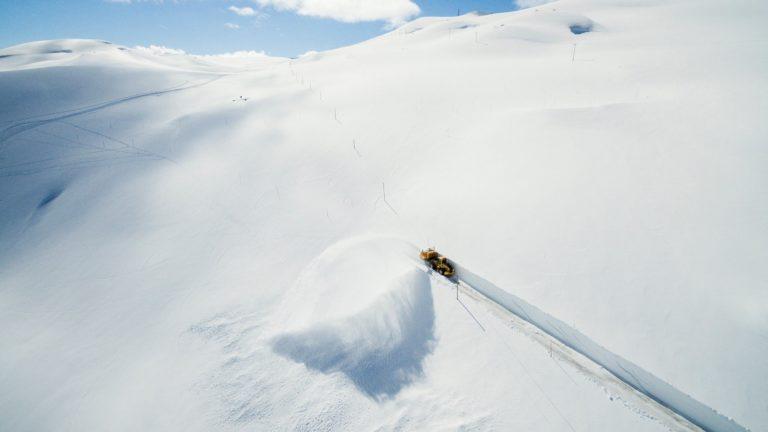 En brøytemaskin brøyter Sognefjells veien for våren på oversiden av Krossbu