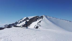 På vei opp med hytta på toppen av Galdhøpiggen bak.